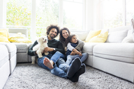 Happy family with dog sitting together in cozy living room - MOEF00369