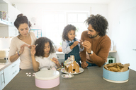 Family pasting gingerbread house in kitchen for Christmas with sweets - MOEF00378