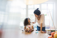 Mother helping daughter with homework, using microscope - MOEF00384