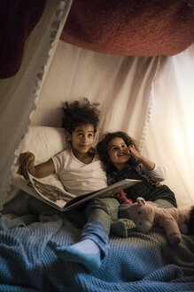 Two sisters sitting in dark children's room, reading a book - MOEF00405