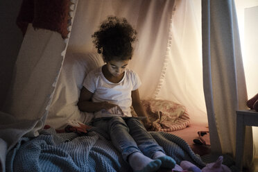 Little girl sitting in dark children's room, looking at digital tablet - MOEF00408