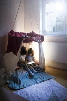 Two sisters sitting in dark children's room, looking at digital tablet - MOEF00411