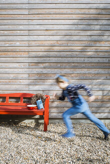 Girl running in front of a wooden facade - OJF00207