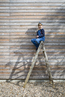 Laughing girl sitting on ladder in front of a wooden facade - OJF00210