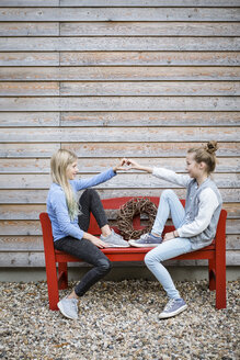 Two best friends sitting on a red bench in front of a wooden facade forming heart with their hands - OJF00216