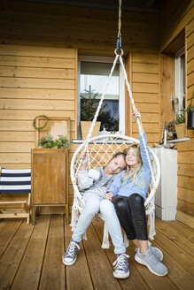 Two girls relaxing in a hanging chair on veranda - OJF00222
