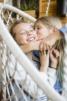 Girl hugging and kissing her best friend in a hanging chair - OJF00225