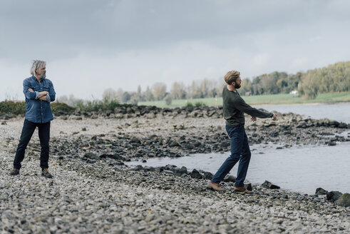 Father and son spending time together, son skipping pebbles - KNSF02926