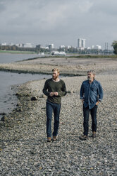 Father and son taking a stroll at Rhine river, meeting to talk - KNSF02932