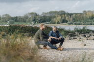 Father and son meeting at Rhine river in autmn, talking together - KNSF02935