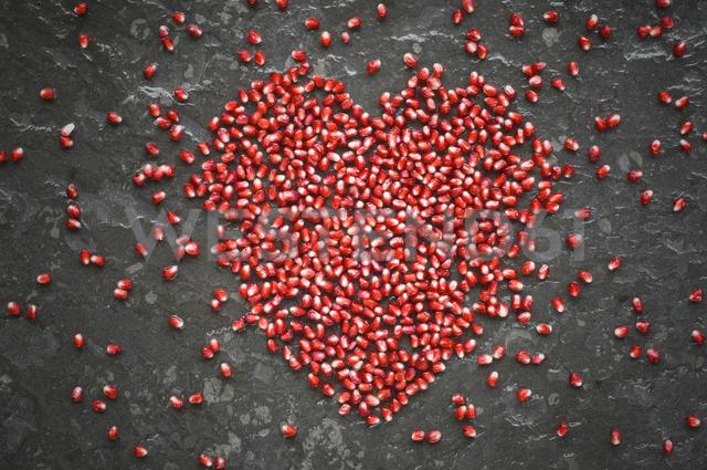 Heart shaped of pomegranate seeds on slate - ASF06124