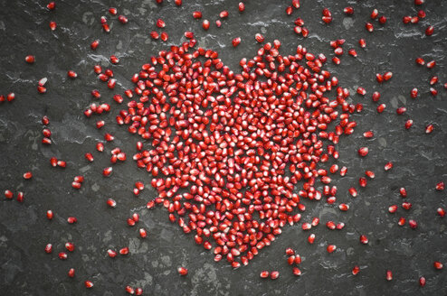 Heart shaped of pomegranate seeds on slate - ASF06124