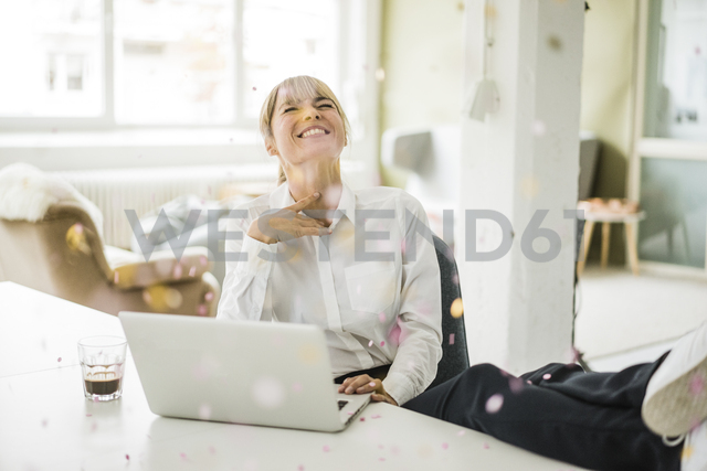 Confetti falling on businesswoman with laptop in office - JOSF01944 - Joseffson/Westend61