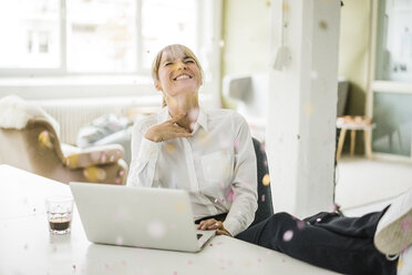 Confetti falling on businesswoman with laptop in office - JOSF01944