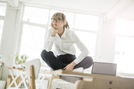 Businesswoman sitting on desk in office thinking - JOSF01947