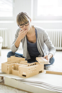 Woman in office looking at architectural model - JOSF01956
