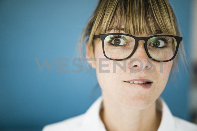 Portrait of woman with glasses biting on her lip - JOSF01968