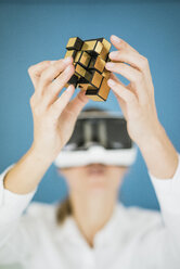 Businesswoman wearing VR glasses holding cubical structure - JOSF01977