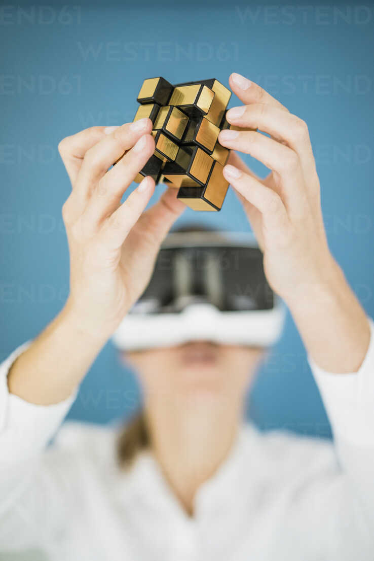 Businesswoman wearing VR glasses holding cubical structure - JOSF01977 - Joseffson/Westend61
