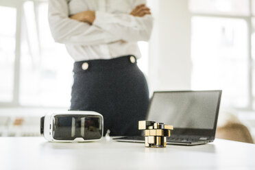 Cubical structure, VR glasses and laptop on office desk with businesswoman in background - JOSF01983