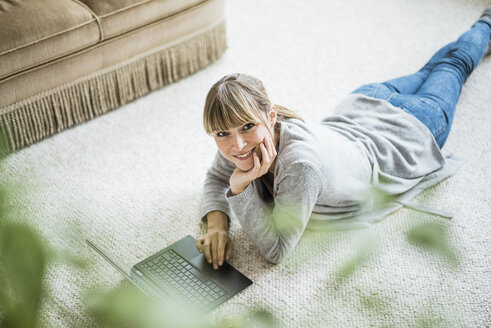 Smiling woman lying on the floor using laptop - JOSF01998