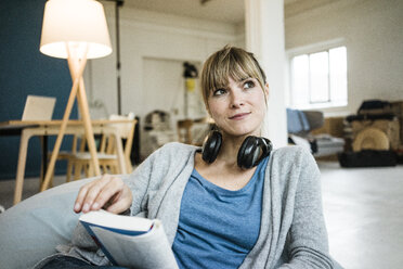 Smiling woman sitting in beanbag with book and headphones - JOSF02004