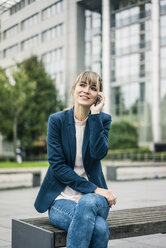Smiling businesswoman sitting on bench talking on cell phone outdoors - JOSF02007