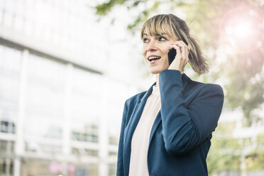 Businesswoman talking on cell phone in the city - JOSF02010