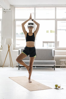 Young woman practising yoga wearing VR glasses - KNSF02975