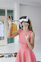 Happy young woman in fashion studio wearing VR glasses - KNSF02984
