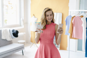 Smiling young woman in fashion studio taking cell phone picture of shopping cart model - KNSF02987