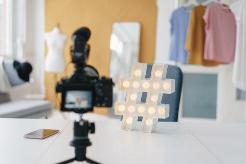Camcorder recording hashtag sign on table in fashion studio - KNSF02990