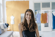 Portrait of happy young woman in fashion studio - KNSF02993