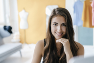 Portrait of smiling brunette young woman in fashion studio - KNSF02996