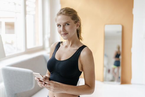 Portrait of smiling young woman in sportswear holding cell phone - KNSF03002