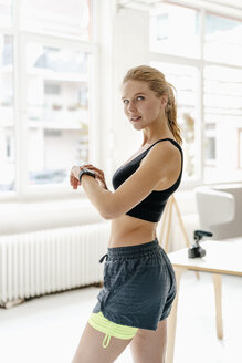 Portrait of confident young woman in sportswear with smartwatch - KNSF03005