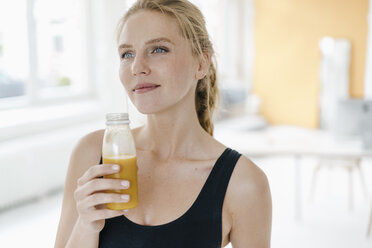 Portrait of smiling young woman in sportswear drinking a smoothie - KNSF03008