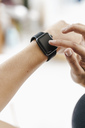 Close-up of woman adjusting her smartwatch - KNSF03011