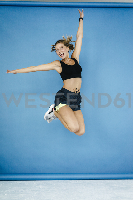 Happy young woman in sportswear jumping midair - KNSF03026