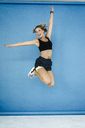 Happy young woman in sportswear jumping midair - KNSF03026