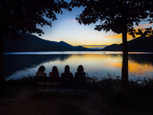 Austria, Upper Austria, Salzkammergut, Lake Fuschlsee, people sitting on bench enjoying sunset - AMF05536