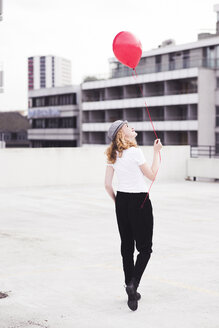 Back view of young woman with red balloon - UUF12327