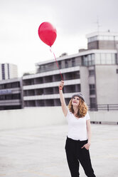 Smiling young woman with red balloon - UUF12330