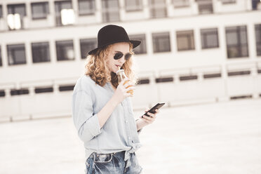 Young woman drinking beverage while using cell phone - UUF12333