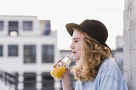 Portrait of young woman with hat drinking beverage - UUF12336