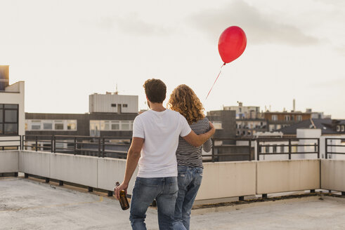 Back view of young couple on roof terrace at evening twilight - UUF12339