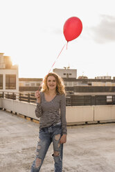 Portrait of young woman with red balloon on roof terrace at sunset - UUF12345