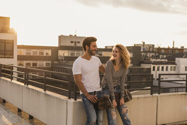 Happy young couple relaxing on roof terrace at sunset - UUF12351