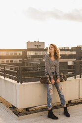 Young woman with skateboard enjoying sunset on roof terrace - UUF12354