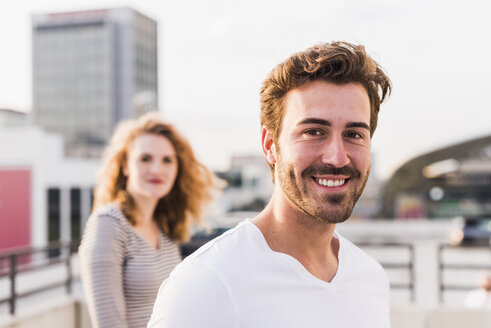 Portrait of happy young man with girlfriend in the background at sunset - UUF12357